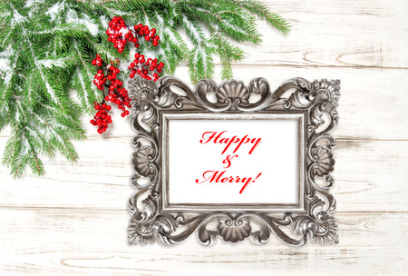 hollyberry: Christmas tree branches with red berries and snow. Vintage picture frame with sample text Happy Merry! Stock Photo