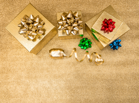 red ribbon bow: Gift boxes with ribbon bow on bright golden background. Holidays decoration. Top view