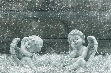 angel de la guarda: Dormir ángel de la guarda. Decoración navideña. estilo vintage tonificado imagen con efecto de nieve cayendo. enfoque selectivo Foto de archivo