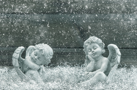 guardian: Sleeping guardian angel. Christmas decoration. Vintage style toned picture with falling snow effect. Selective focus