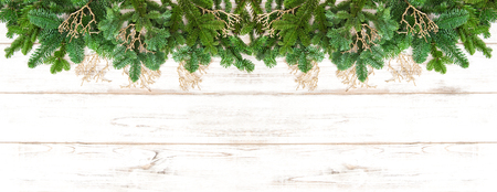 branch of a christmas tree: Christmas tree branches with golden decoration on wooden texture. Winter holidays banner