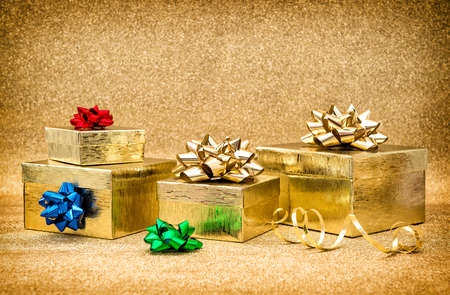 red ribbon bow: Gift boxes with ribbon bow on golden shiny background. Colorful holidays decoration. Vintage style toned picture