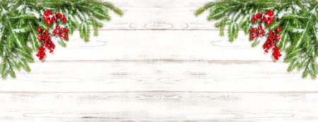 hollyberry: Christmas tree branches on wooden background. Festive decoration. Winter holidays banner