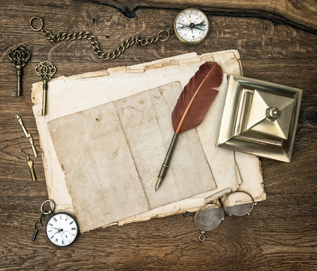pen on paper: Antique office supplies and writing tools on wooden desk. Vintage keys, clock, glasses, feather pen, compass