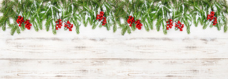 hollyberry: Christmas decoration. Holidays banner. Evergreen tree branches with red berries on wooden background Stock Photo