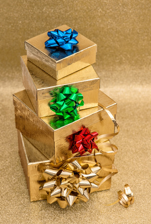 red ribbon bow: Gift boxes with ribbon bow on bright golden background. Colorful holidays decoration