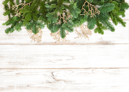 branch of a christmas tree: Christmas tree branches with golden decoration on wooden texture. Winter holidays background Stock Photo