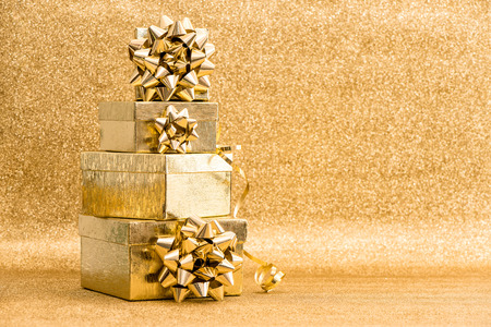 gift ribbon: Gift boxes with ribbon bow on golden shiny background. Holidays decoration. Greetings card concept