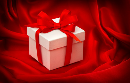 red gift box: Gift box with bow ribbon on red silk background