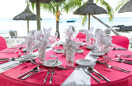 place setting: Romantic dinner on sunset beach. Festive pink table place setting. Selective focus