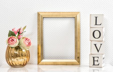 額縁とピンクのバラ。バレンタインの日の概念。ゴールデン フレームと画像やテキストのためのスペースを持つ花のモックアップします。