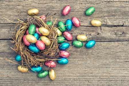 osterei: Easter decoration. Chocolate eggs in nest on wooden background. Vintage style toned picture Lizenzfreie Bilder