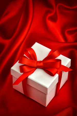 red ribbon bow: White gift box with red ribbon bow. Valentines Day