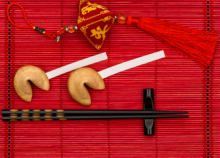 lucky charm: Chinese new years lucky charm, fortune cookies and black chopsticks on red bamboo mat