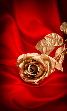 red background: Golden rose flower on red satin background