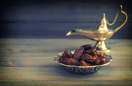 Dates in golden bowl and arabian Aladdin lamp on wooden background. Vintage style toned picture