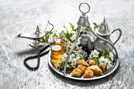 Islamic holidays food with decoration. Ramadan kareem. Eid mubarak. Oriental hospitality concept. Tea glasses and pot, traditional delight baklava