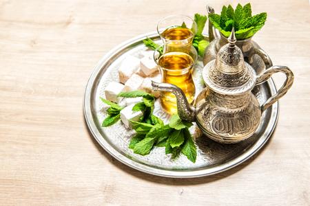 hospitality: Tea with mint leaves and traditional turkish delight. Oriental hospitality concept. Holidays table setting. Ramadan kareem