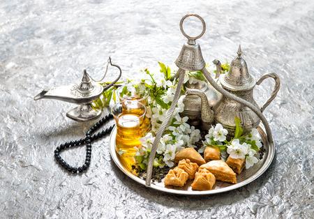 arab spring: Ramadan kareem. Eid mubarak. Islamic holidays decoration. Oriental hospitality concept. Tea glasses and pot, traditional delight baklava