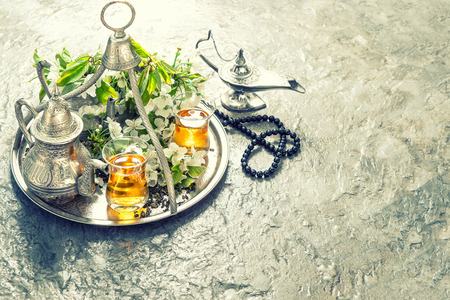 różaniec: Tea table setting with arabian lantern and rosary. Islamic holidays decoration. Oriental hospitality concept. Vintage style toned picture Zdjęcie Seryjne