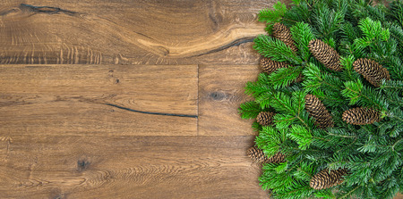 undecorated: Christmas tree branches over rustic wooden background. green border from undecorated evergreen twigs