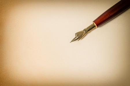 pluma de escribir antigua: Antique ink pen on grungy paper texture. Vintage background with space for your text. Retro style toned picture Foto de archivo