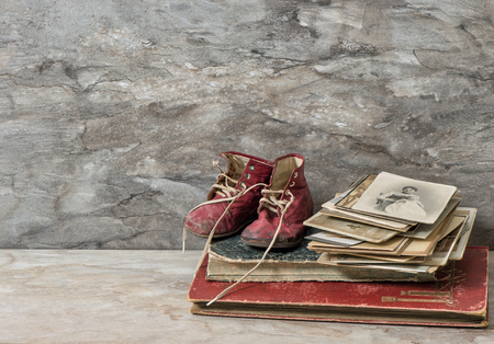 Antique books, photos, and baby shoes. Nostalgic still life with stone background
