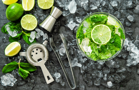 wine making: Mojito cocktail ingredients lime, mint leaves, ice. Drink making accessories