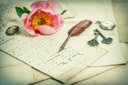 sentimental: Old handwritings, antique feather pen, keys, pocket watch and pink peony flower. Sentimental vintage background. Selective focus. Retro style toned picture Stock Photo