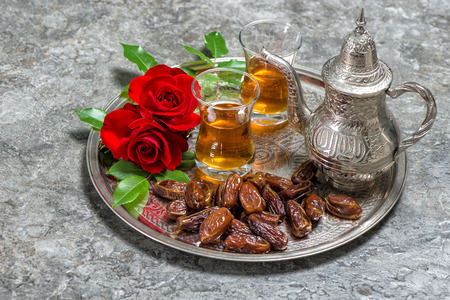 hospitality: Tea, dates fruits and red rose flowers. Islamic holidays decoration. Ramadan kareem. Eid mubarak. Oriental hospitality concept. Slective focus