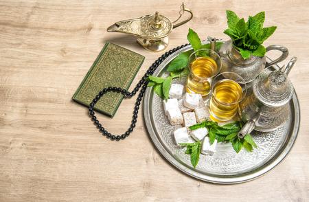 arab spring: Islamic holidays decoration. Ramadan kareem. Tea glasses and pot, arabian lantern, holy book quran and rosary. Oriental hospitality concept