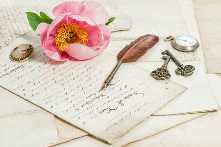 sentimental: Old handwritings, antique feather pen, keys, pocket watch and pink peony flower. Sentimental vintage background. Selective focus Stock Photo
