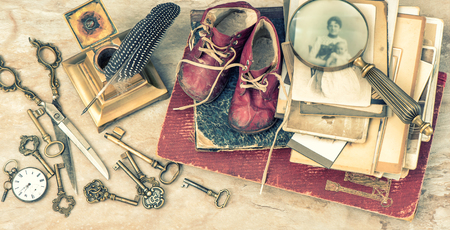 photo album page: Antique books and photos, keys and writing accessories. Nostalgic still life with baby shoes. Vintage style toned picture Stock Photo