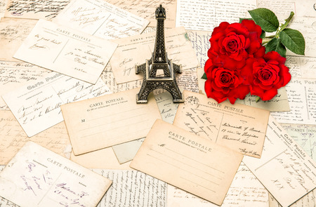 old letters: Red roses, old letters and souvenir Eiffel Tower from Paris. Nostalgic holidays background Stock Photo