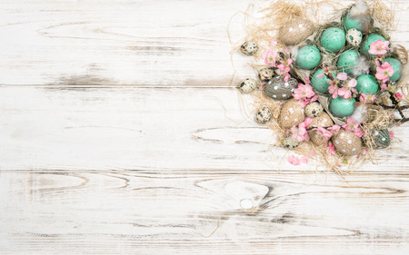 Easter decoration with eggs and flowers on bright wooden background