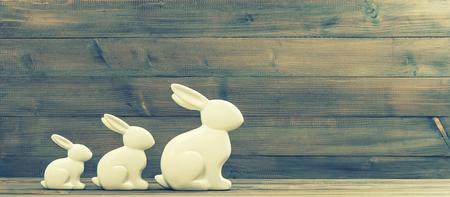 huevos de pascua: White easter bunnies on rustic wooden background. Retro style toned picture Foto de archivo