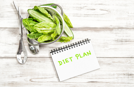 green salad leaves and vegetables with diet plan journal on white