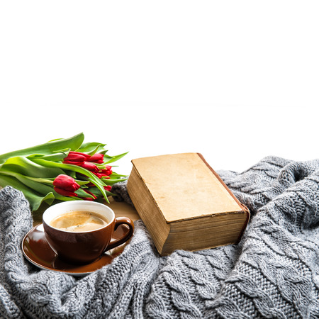 coziness: Cup of coffee, old book and tulip flowers. Coziness concept