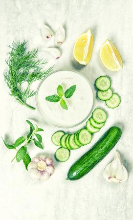 tzatziki: Tzatziki sauce ingredients. Food background. Vintage style toned picture