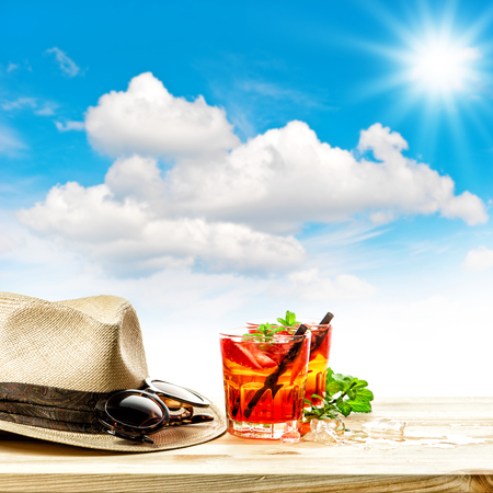 tropical drink: Red tropical drink and green mint leaves. Summer holidays concept sunny blue sky