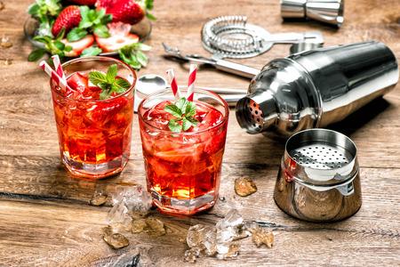 cocteles de frutas: La bebida roja con hielo. herramientas de la barra de toma de cóctel, fresa y hojas de menta Foto de archivo