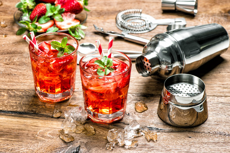 Red drink with ice. Cocktail making bar tools, strawberry and mint leaves 免版税图像