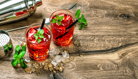 Red cocktail with ice, mint leaves and strawberry on wooden background