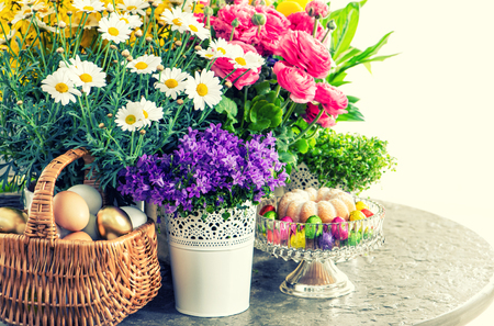 Easter decoration with flowers, eggs and cake. Vintage style toned picture