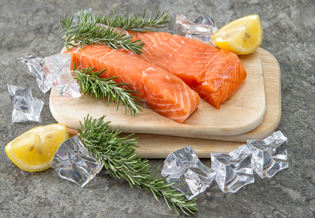 salmon fishery: Raw salmon fillet with fresh herbs, lemon and ice. Seafood. Fish. Healthy nutrition