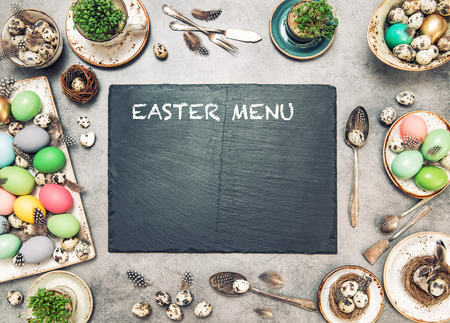 Easter table decoration with colored eggs and stone plate. Holidays background with space for your text