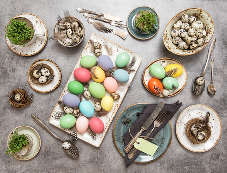 a place of life: Easter still life. Festive table place setting decoration with colored eggs. Top view
