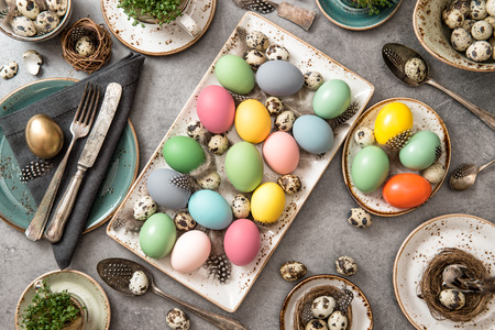 place setting: Easter table place setting decoration with colored eggs. Top view Stock Photo