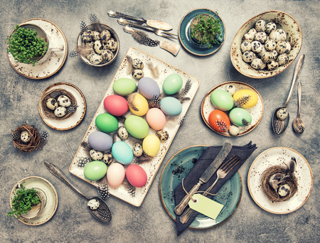 a place of life: Easter still life. Festive table place setting decoration with colored eggs. Vintage style toned picture