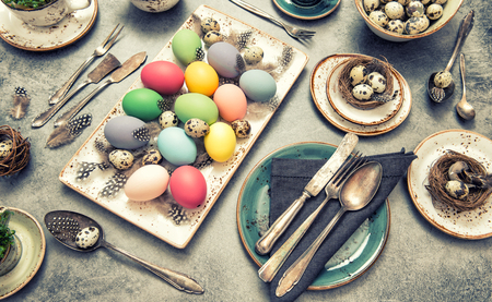 place setting: Table place setting decoration with colorful eggs. Easter dinner. Vintage style toned picture